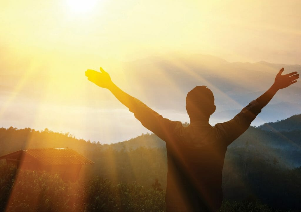 A man standing On the mountain in front of the Sun_ Spiritual