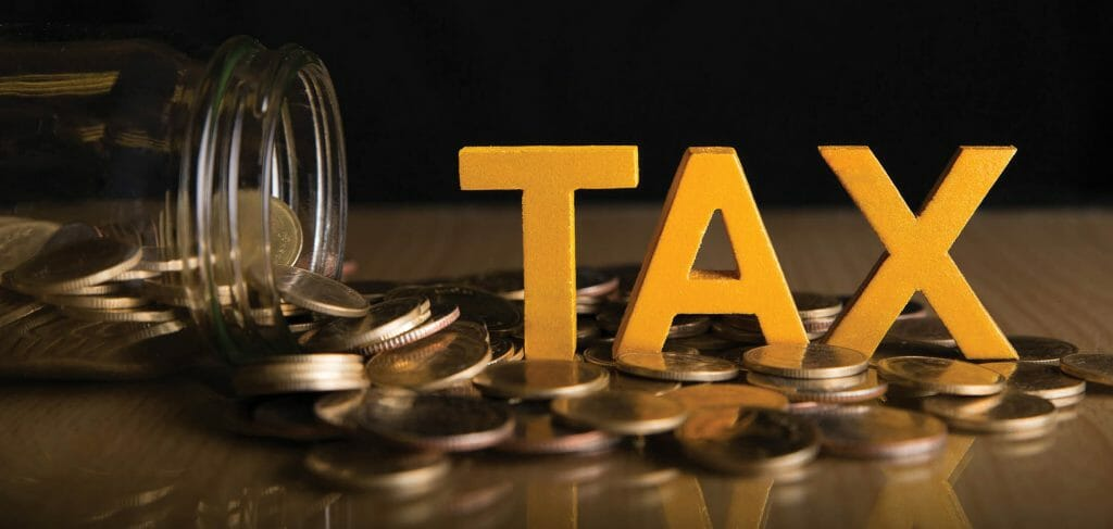 Tax Concept.Word tax put on coins and glass bottles with coins inside on black background