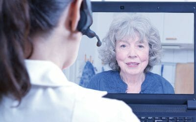 Female doctor of geriatrics with headset in front of her laptop during an consultation over the internet with a senior patient, telemedicine concept