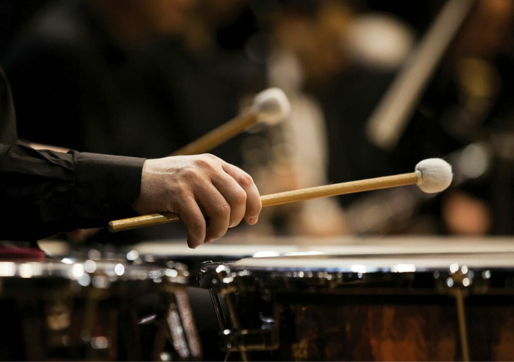 Hands musician playing the timpani in the orchestra closeup in dark colors