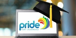 Black yellow tassel hat of graduation on computer table with notebook With Pride Fort Lauderdale logo on Laptop screen