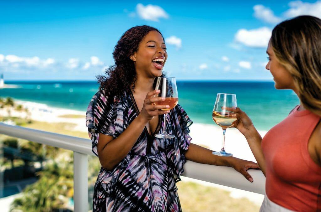 LauderDeals_LauderDeals getaway_2 women on the patio by the beach drinking